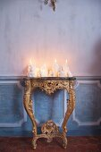 Arrangement of white candles of various shapes on antique gilt console table