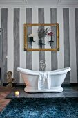 White, free-standing bathtub below gilt picture frame and ornaments on grey-striped wall