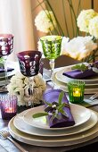 Flower arrangement, tealight and wineglasses on festively set table