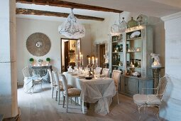 Festively set, candlelit dining table in front of glass-fronted cabinet in historical interior