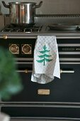 Tea towel with embroidered Christmas tree hung on black gas cooker