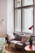 Sofa with scatter cushions, side table and standard lamp below window in period apartment