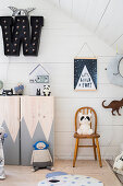 Wooden cabinet with painted doors and various wall decorations in attic room with white wood panelling