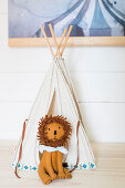 Small cloth lion in front of teepee on top of cabinet in child's bedroom