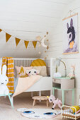 Babybett und Tierfiguren im Dachgeschoss-Kinderzimmer