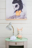 Lamp and animal soft toy on vintage bedside table below poster on wall