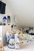 Animal soft toys in wire basket in front of cabinet in child's attic bedroom