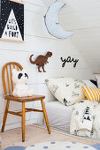 Vintage panda lamp on chair next to bed in child's attic bedroom