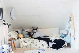 Soft toys on child's bed in child's attic bedroom