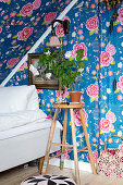 Stool next to bed under sloping ceiling covered with floral wallpaper