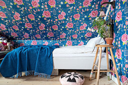 Bed under sloping ceiling covered in floral wallpaper