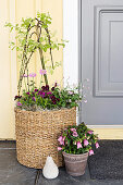Spring flowers in basket and flower pot next to front door