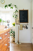 Chalkboard next to climbing plant in open doorway leading into kitchen