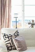 Pudertöne im Wohnzimmer und grafisch gemustertes Kissen