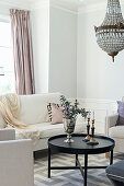 Pale sofa set and chandelier in elegant living room