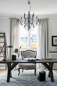 Wooden table and chandelier in elegant study