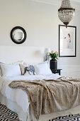 Fellplaid auf dem Bett im eleganten Schlafzimmer in Schwarz-Weiß