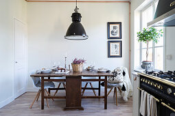 Alter Holztisch mit modernen Stühlen in der Küche mit Gasherd