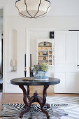 Round wooden table on zebra-skin rug in front of open panelled door