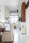 Wohnküche im eleganten Landhausstil mit weißem Holzboden