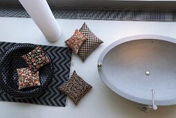 Mixture of patterns on cushions and rug next to oval bathtub
