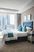 Bed with upholstered blue frame and beige carpet in elegant bedroom