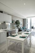 Fitted kitchen and set white dining table in open-plan interior