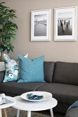 Grey sofa with turquoise scatter cushions below framed photos on beige wall