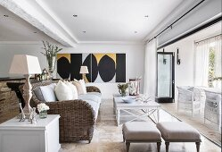 Modern artworks in elegant country-house-style lounge with open terrace doors