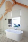 Free-standing white bathtub below window in gable wall in bright, modern bathroom
