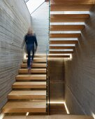 Woman walking up floating wooden staircase