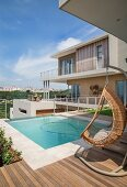 Pool and wicker hanging chair on summer terrace