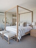 Four-poster bed against patterned wallpaper and antique chest of drawers in country-house-style bedroom