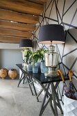 Elegant table lamps on black console table in hallway against black and white wall