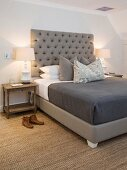 Sisal rug and grey button-tufted headboard in bedroom