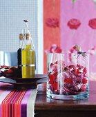 Radicchio mit Rosenblättern in Glasschale und Olivenöl auf Holztisch