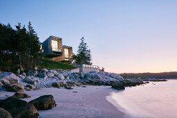 Two modern beach-houses on coast at twilight