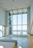 High-ceilinged room with panoramic window and sea view