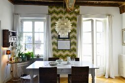 Dining area in front of retro wallpaper in period apartment