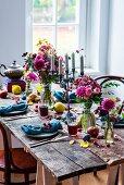 Gedeckter Holztisch herbstlich rustikal dekoriert mit Blumen und Früchten