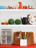 Colourful retro crockery, watermelons and trays on white kitchen shelves