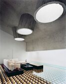 Round concrete skylights and geometric floor tiles with 3D-effect pattern in unusual lounge area