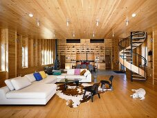 Open-plan interior of wooden house with elegant lounge area, spiral staircase and fitted shelving
