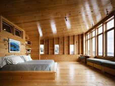 Double bed in spacious bedroom in wooden house