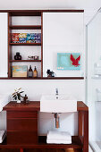 Dark wood vanity and wall shelf with mirror cabinet in the bathroom