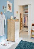 Kommode an hellblauer Wand im Schlafzimmer, im Hintergrund begehbare Garderobe mit Schiebetür