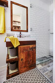 Old vanity unit in the bathroom with white subway tiles