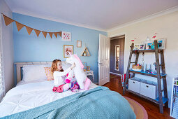 Girl plays on bed, DIY shelf made of old wooden ladder in children's room with light blue wall
