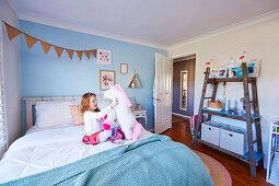 Mädchen spielt auf dem Bett, DIY-Regal aus alter Holzleiter im Kinderzimmer mit hellblauer Wand