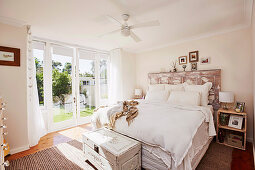 Double bed with DIY bed head from old wooden door in bright bedroom with garden access